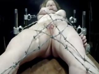 The Master ties his submissive to the table with the help of barbed wire. She can not even move because the wire immediately pierces her flesh. Even her labia are attached to the wire.